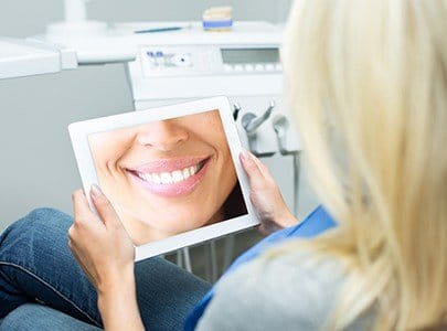 Woman looking at her cosmetic dentistry plan on tablet compter