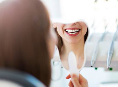 Woman looking at smile in mirror after smile makeover