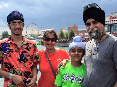 Dr. Singh and his family smiling outdoors